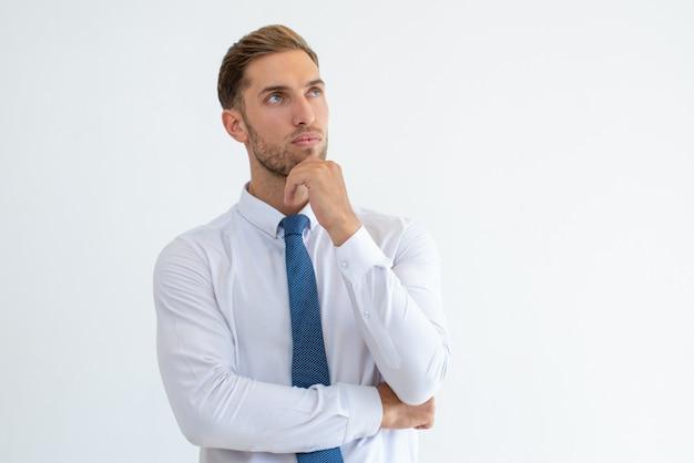 Uomo d'affari pensoso toccando il mento e guardando lontano