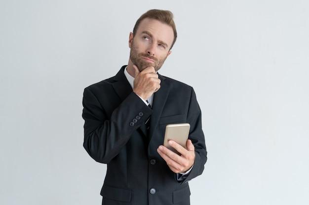 Uomo d'affari pensoso toccando il mento, pensando e tenendo smartphone.