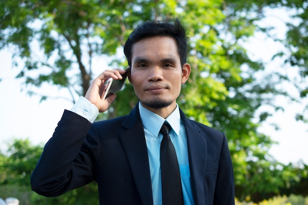 Uomo d'affari people che tiene smart phone mobile e telefono di conversazione