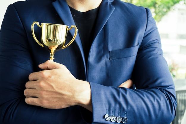 Uomo d'affari per essere vincitore tenendo premio trofeo con successo e realizzazione