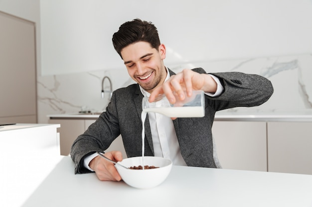 Uomo d'affari piacevole seduto al tavolo in cucina e