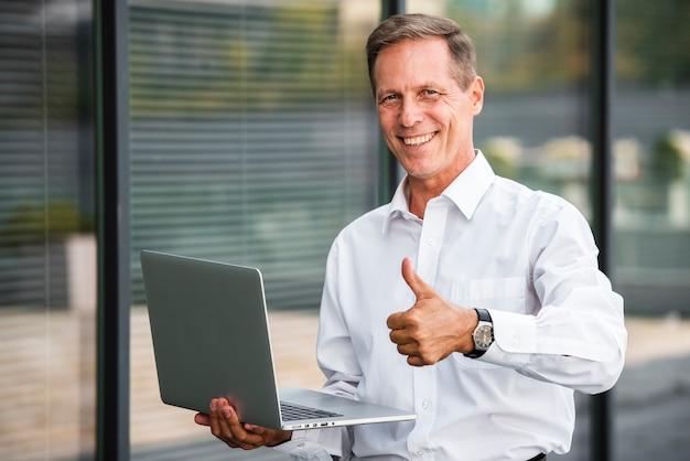 Uomo d'affari pollice in alto tenendo portatile