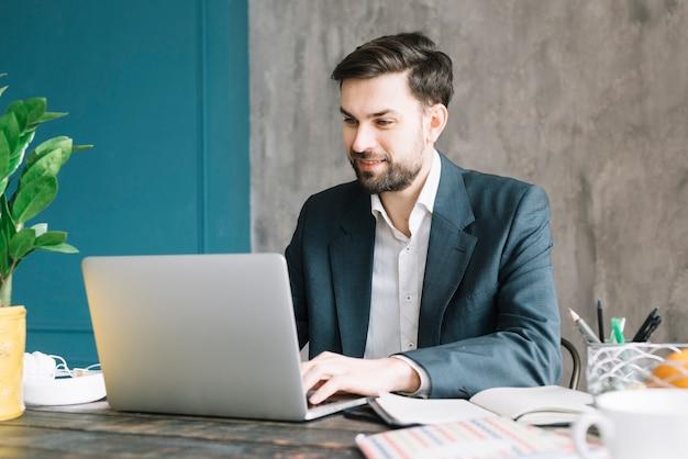 Uomo d'affari positivo che per mezzo del computer portatile