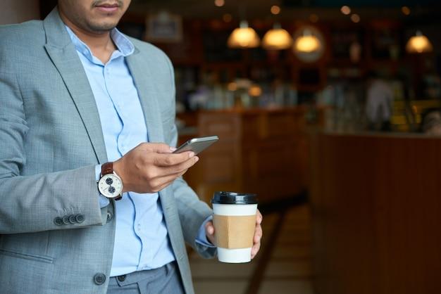 Uomo d'affari potato che controlla posta del telefono che tiene la tazza di caffè asportabile di mattina