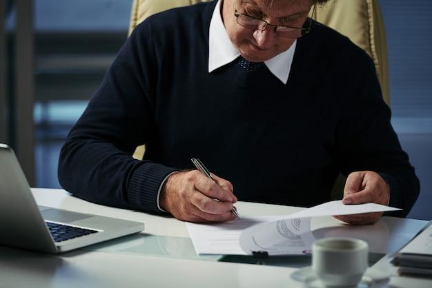 Uomo d'affari potato che esamina i documenti per la vendita di affari
