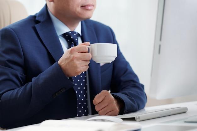 Uomo d'affari potato che mangia caffè alla sua scrivania che esamina lo schermo del computer