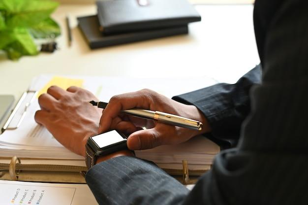 Uomo d'affari potato del colpo facendo uso dell'orologio astuto sulla scrivania