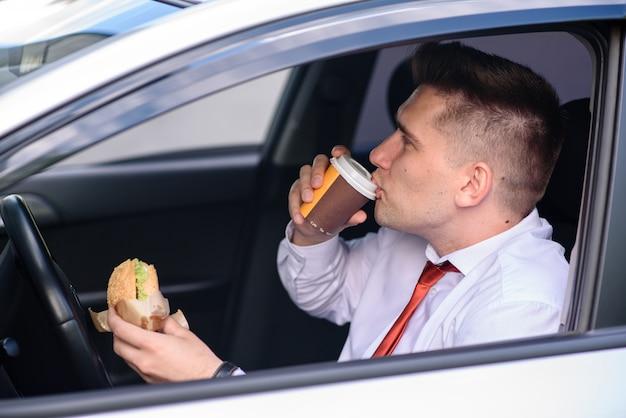 Uomo d'affari pranzare e beve caffè in macchina.