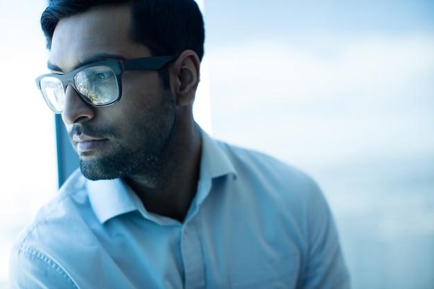 Uomo d'affari premuroso che guarda lontano mentre indossa gli occhiali