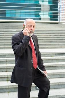 Uomo d'affari premuroso che parla sul telefono