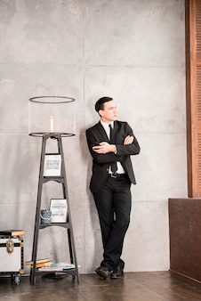 Uomo d'affari premuroso con braccia incrociate guardando lontano