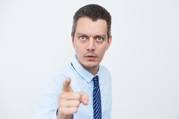 Uomo d'affari preoccupato che punta con il dito indice