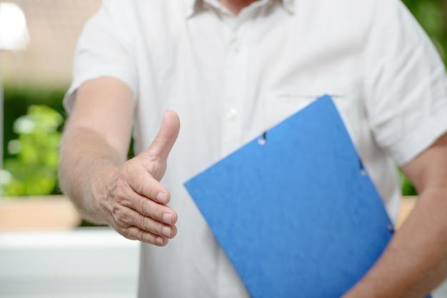 Uomo d'affari pronto alla stretta di mano che sta nell'ufficio