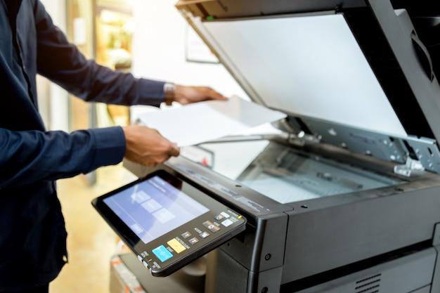 Uomo d'affari pulsante a mano sul pannello della stampante.