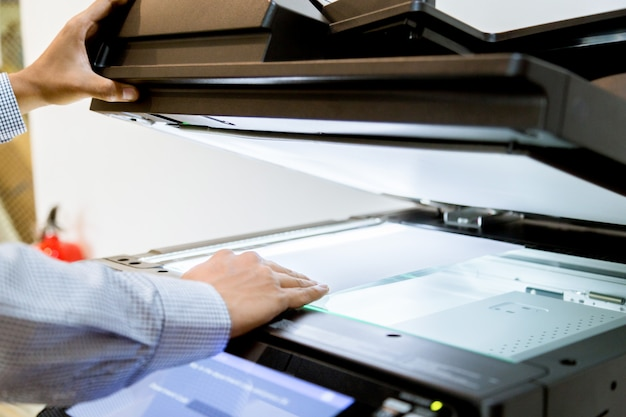 Uomo d'affari pulsante di mano sul pannello della stampante, stampante laser scanner ufficio macchina copia inizio