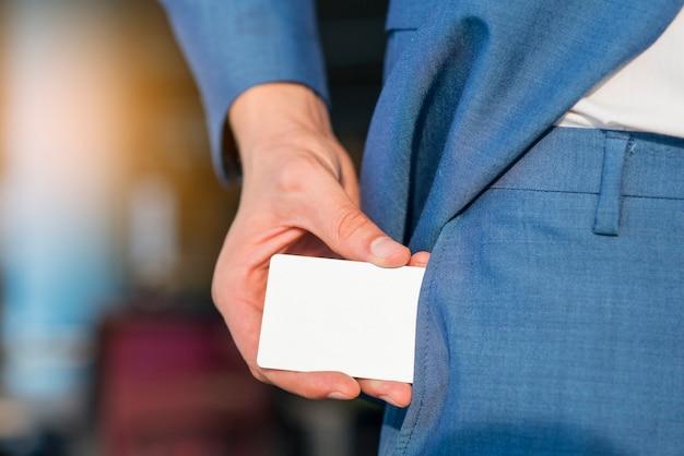 Uomo d'affari rimuovendo la carta bianca in bianco dalla sua tasca