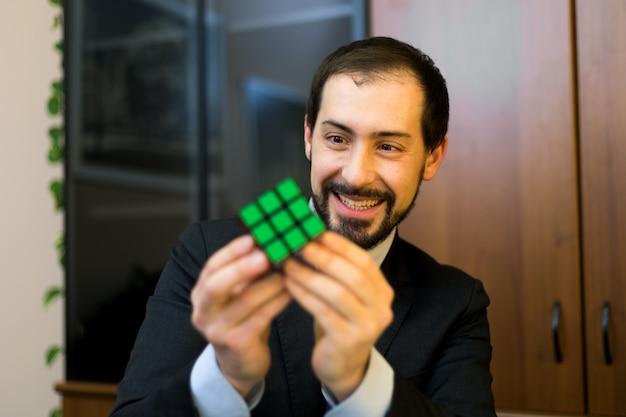 Uomo d'affari risolve il cubo di rubik