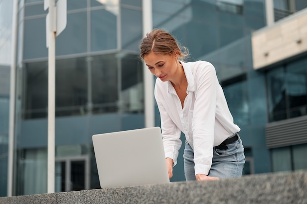 Uomo d'affari riuscito della donna della donna di affari all'aperto con il computer portatile delle cellule