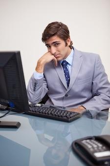 Uomo d'affari seduto annoiato nel suo posto di lavoro
