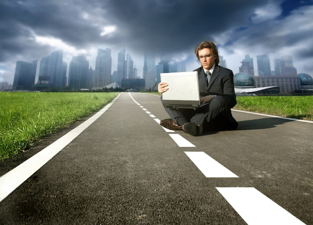 Uomo d'affari seduto su una strada che lavora al computer portatile con la città