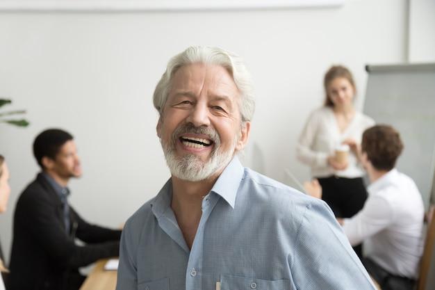 Uomo d'affari senior felice che ride esaminando macchina fotografica in ufficio, ritratto