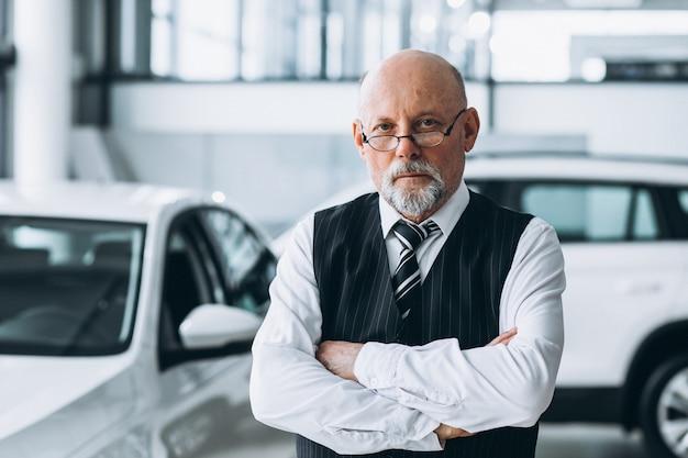 Uomo d'affari senior in una sala d'esposizione dell'automobile