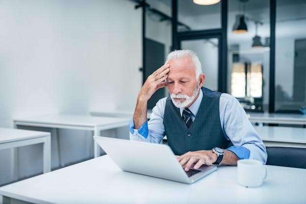 Uomo d'affari senior preoccupato che esamina lo schermo del computer portatile in ufficio moderno.