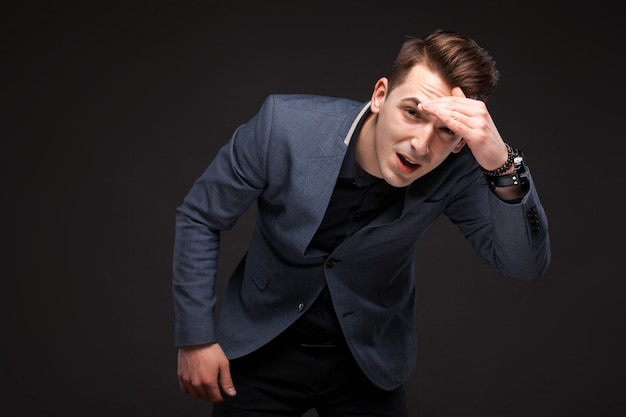 Uomo d'affari serio bello in giacca grigia, orologio costoso e camicia nera