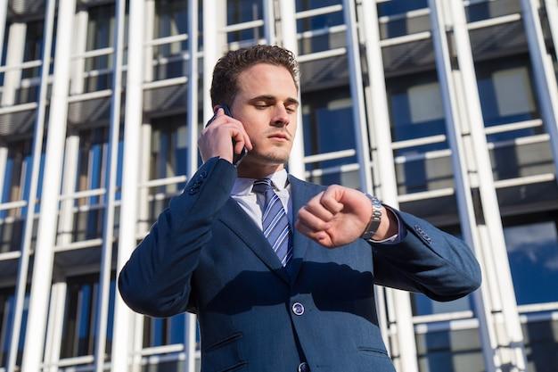 Uomo d'affari serio che controlla tempo che parla sul telefono.