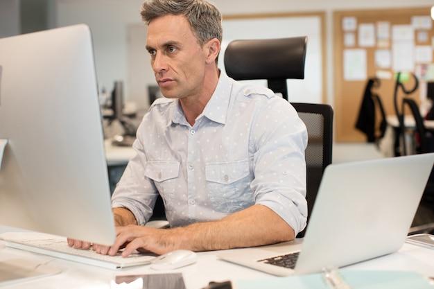 Uomo d'affari serio che digita sul computer in ufficio