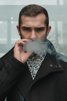 Uomo d'affari serio che fuma nervosamente fuori dall'edificio per uffici.