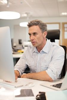 Uomo d'affari serio che lavora al computer in ufficio