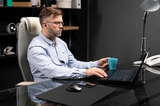 Uomo d'affari serio che lavora al computer portatile e che beve caffè