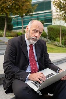 Uomo d'affari serio con lo sguardo del computer portatile