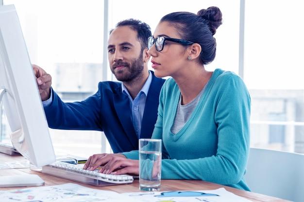 Uomo d'affari serio e donna di affari che discutono sopra il computer all'ufficio creativo