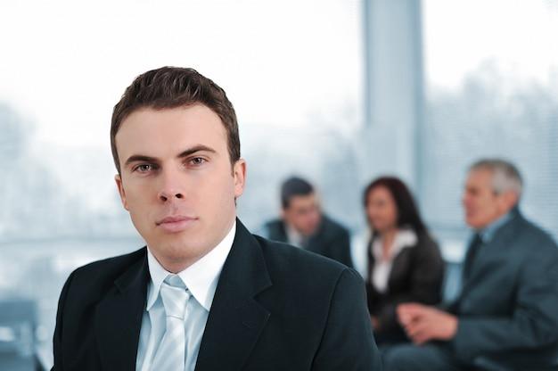 Uomo d'affari serio in compagnia dei colleghi