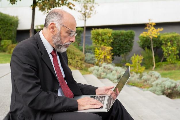 Uomo d'affari serio in occhiali facendo uso del computer sulla via