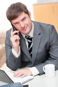 Uomo d'affari sicuro che comunica sul telefono e che per mezzo del suo computer portatile
