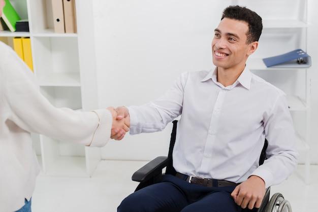 Uomo d'affari sicuro che si siede sulla sedia a rotelle che stringe le mani con il suo collega femminile