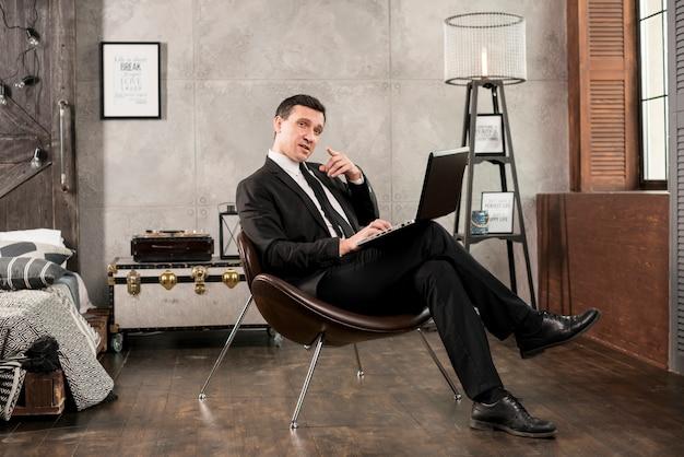Uomo d'affari sicuro con il computer portatile che indica alla macchina fotografica