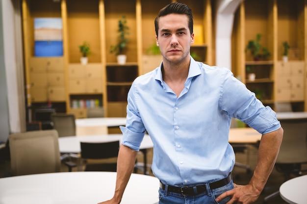 Uomo d'affari sicuro con la mano sull'anca nella sala riunioni