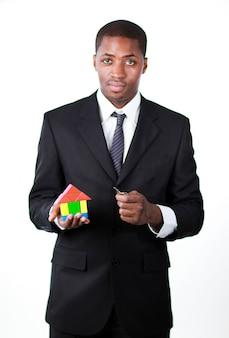 Uomo d'affari sicuro con una casa per un concetto del bene immobile