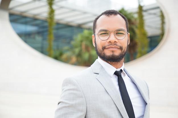 Uomo d'affari sicuro positivo che posa fuori