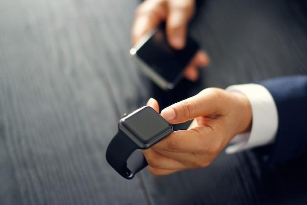 Uomo d'affari sincronizzazione, accoppiamento o abbina smartwatch con lo smartphone