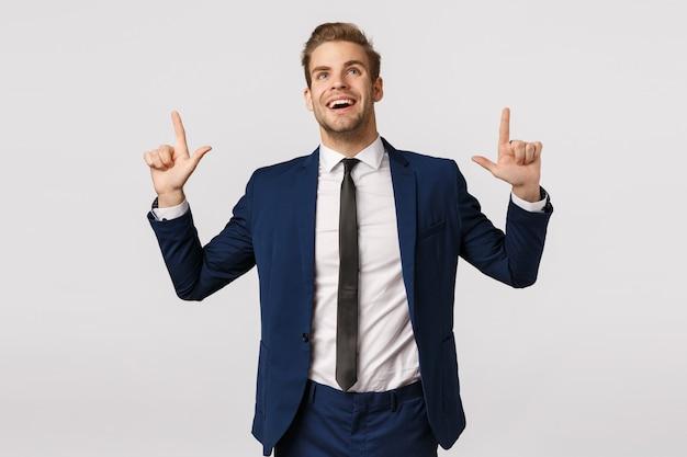 Uomo d'affari sognatore e ottimista, vedendo la possibilità di prosperità, sorridendo e alzando lo sguardo eccitato, contemplare uno splendido scenario, catturato l'attenzione sul promo del prodotto, in piedi felice sfondo bianco