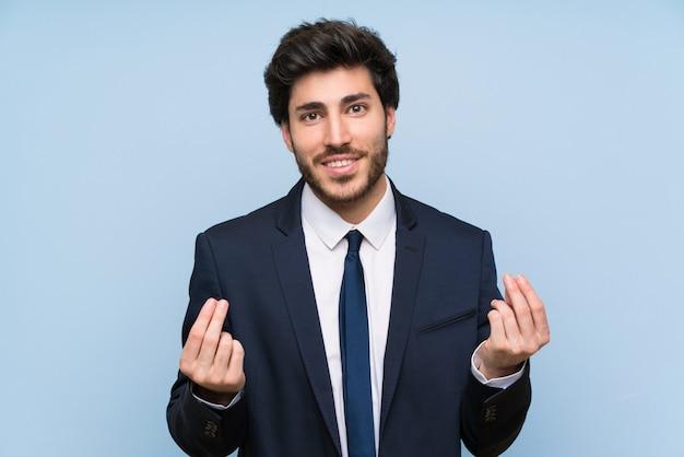 Uomo d'affari sopra la parete blu isolata che fa gesto dei soldi