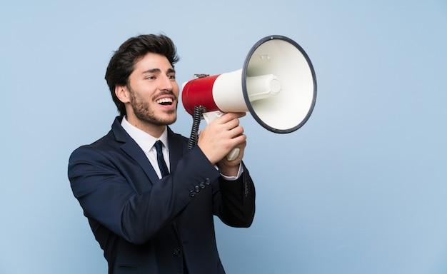 Uomo d'affari sopra la parete blu isolata che grida tramite un megafono