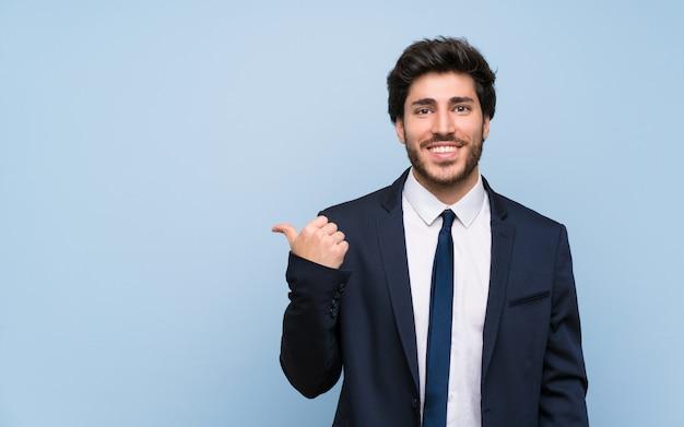 Uomo d'affari sopra la parete blu isolata che indica il lato per presentare un prodotto