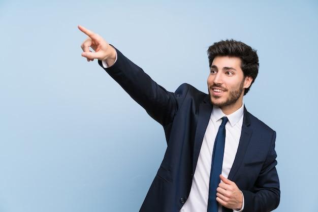 Uomo d'affari sopra la parete blu isolata che indica via