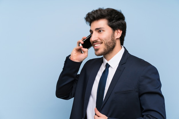 Uomo d'affari sopra la parete blu isolata che mantiene una conversazione con il telefono cellulare